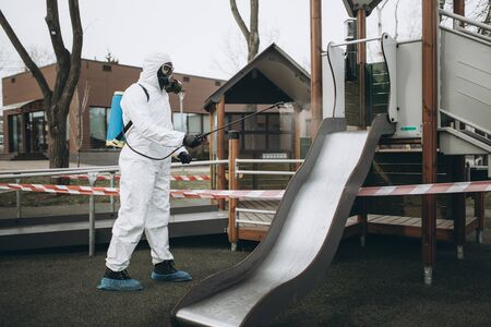 Cleaning and Disinfection on the playground in the sity complex amid the coronavirus epidemic Professional teams for disinfection efforts Infection prevention and control of epidemic Protective suit and mask and spray bag,