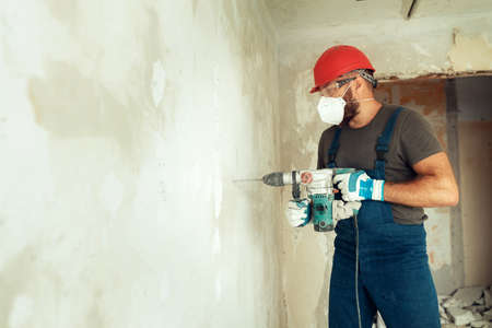 builder with perforator drills holes in concrete wall The builder is dressed in a protective suit and helmet