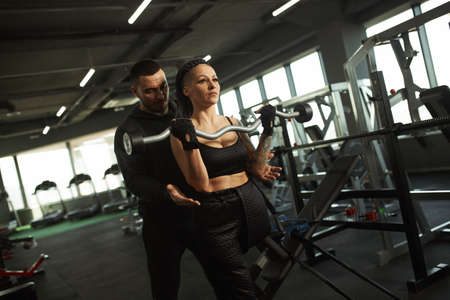 A disabled girl is engaged in the gym A woman with one leg trains with a trainer, she works hard and does not give up in front of trouble Zdjęcie Seryjne