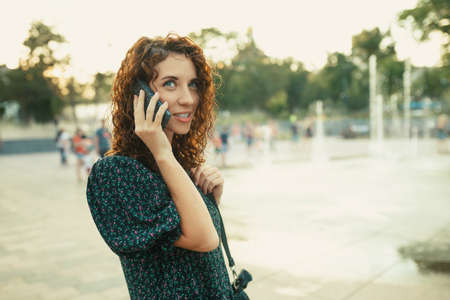 Portraits of a charming red-haired girl with a pretty face. The girl talks cutely with someone on the phone. She has a great mood and a sweet smile