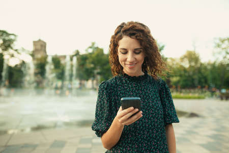 Portraits of a charming red-haired girl with a pretty face. The girl looks at her phone. She has a great mood and a sweet smile Zdjęcie Seryjne