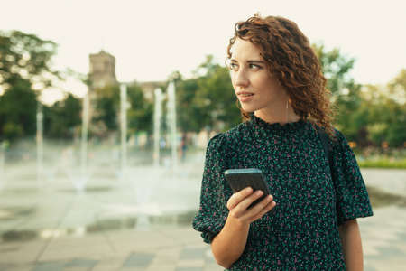 Portraits of a charming red-haired girl with a pretty face. The girl holds a mobile phone in her hands and looks to the side. She has a great mood and a sweet smile