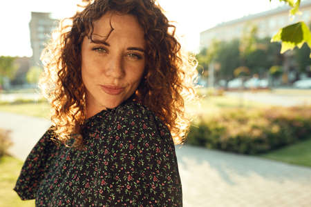 Portraits of a charming red-haired girl with freckles and a pretty face. The girl poses for the camera in the city center. She has a great mood and a sweet smile