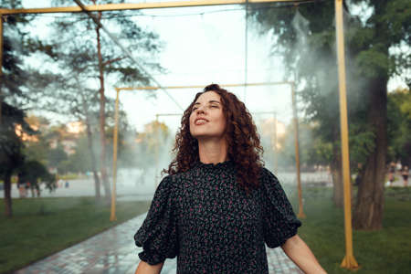 cute red-haired curly girl rejoices under the water mist in the city center Zdjęcie Seryjne