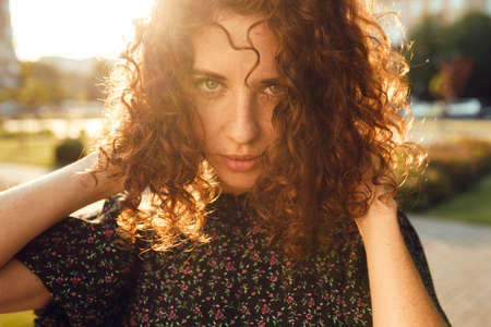 charming curly red-haired girl with freckles in dress poses for the camera in the city center showing different facial emotions Zdjęcie Seryjne