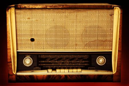 Old radio on a red background photo