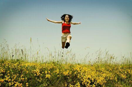 Beautiful young woman jumping photo