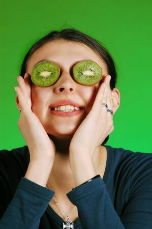 Pretty young woman holds kiwi in front of her eyes  photo