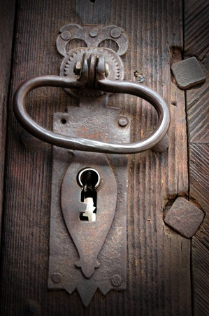 A very old door handle on a wooden door  photo