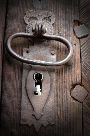 A very old door handle on a wooden door  photo