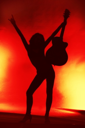 Woman with guitar silhouette on red background Reklamní fotografie - 11742232