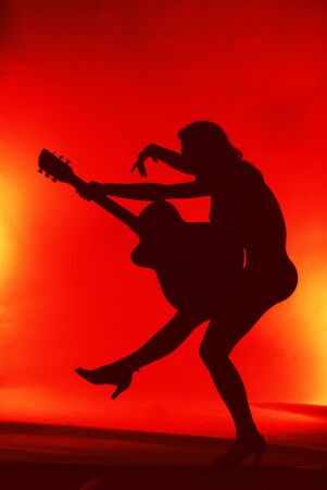 Woman with guitar silhouette on red background  photo