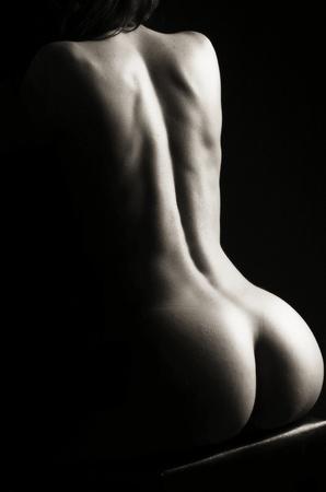 mujer desnuda de espalda: Hermoso culo de una mujer joven sobre fondo oscuro