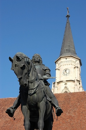 kolozsvar:  Statue of King Mathias (Matyas, Matei, Corvinus) in the center of Cluj Napoca. Saint Michaels gothic church in the background. Transylvania, Romania