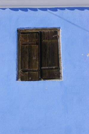 Blue wall with a wooden window                                 photo