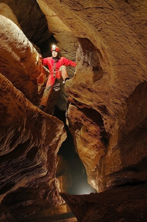 Cave passage with caver Stock Photo