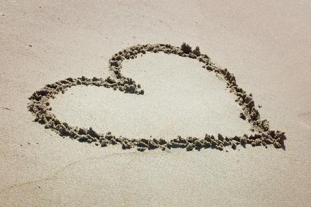 Handwritten heart on sand photo