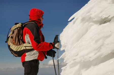 Climber on summit near a cross with frost ice crystals photo