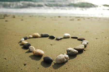 Heart gemaakt van stenen op een zand achtergrond