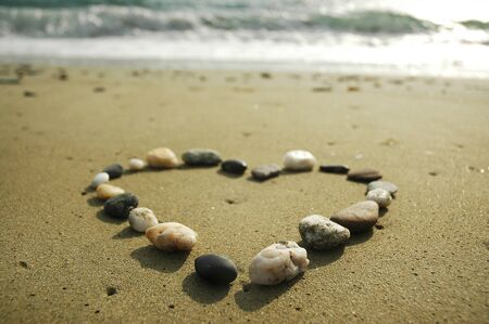 Heart made of stones on a sand background