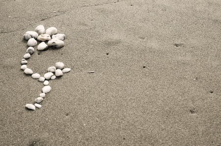 Flower made of stones on a sand background photo