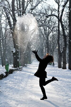 Young woman enjoying winter and playing with snow photo