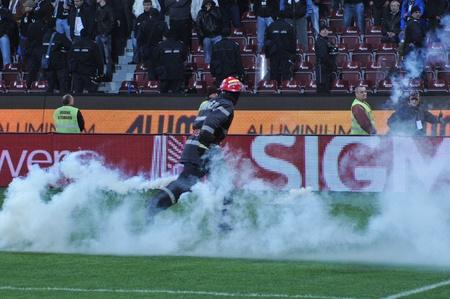 fanatics: CLUJ-NAPOCA, ROMANIA - APRIL 14: Fireman runs among flairs during a Romanian Championship derby between CFR Cluj - Universitatea Cluj at the C. Radulescu Arena on Apr. 14, 2011 in Cluj