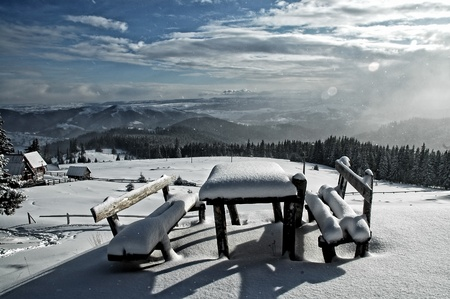 Snow covered table and benches in the mountains  photo