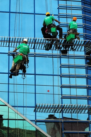 CLUJ NAPOCA – MAY 03: Unidentified workers washing the windows facade of a new build bank before the official opening on May 03, 2011 in Cluj Napoca, Romania Stock Photo - 12272485