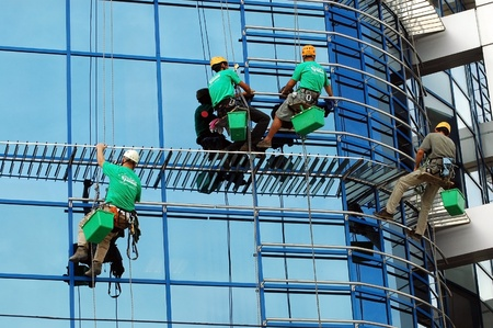CLUJ NAPOCA � MAY 03: Unidentified workers washing the windows facade of a new build bank before the official opening on May 03, 2011 in Cluj Napoca, Romania Stock Photo - 12272472