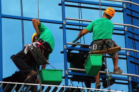 CLUJ NAPOCA – MAY 03: Unidentified workers washing the windows facade of a new build bank before the official opening on May 03, 2011 in Cluj Napoca, Romania