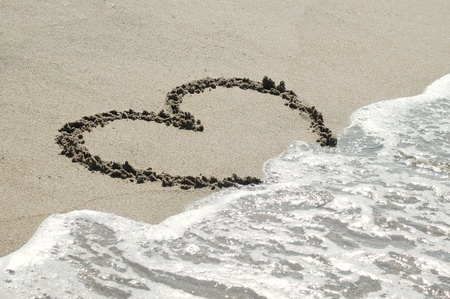 Handwritten heart on sand with wave approaching