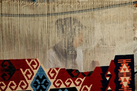 Göreme, Turkije - CIRCA JULI 2006: Vrouw weeft een traditioneel Turks tapijt, in Goreme, Turkije. De tapijten zijn met de hand geweven, en ze nemen een lange tijd te produceren. Circa juli 2006 in Goreme, Turkije