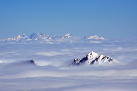 Peaks above clouds, winter in the Austrian Alps photo