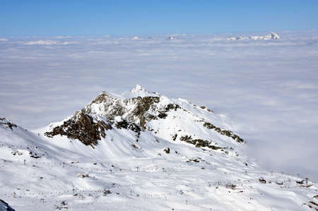 Clouds and fog above, beautiful sunny winter landscape in the Austrian Alps. Kitzsteinhorn, Austria photo