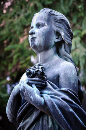 Young girl statue holding a bouquet of flowers, Salzburg cemetery, Austria Stock Photo - 12669503