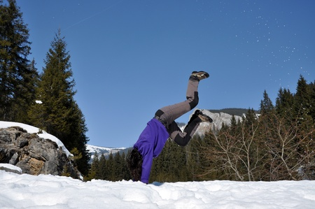 Young woman doing a cartwheel in the snow, in the mountains at winter photo
