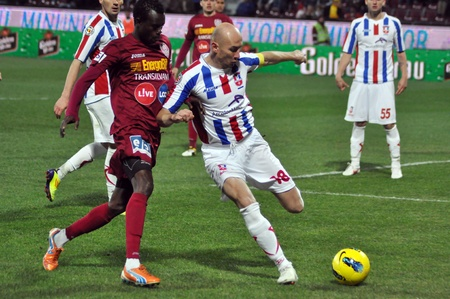 galati: CLUJ-NAPOCA, ROMANIA – MARCH 26: M.Sougou (red) and V. Costin (white) in action at a Romanian National Championship soccer game CFR Cluj vs. Otelul Galati, March 26, 2012 in Cluj-Napoca, Romania