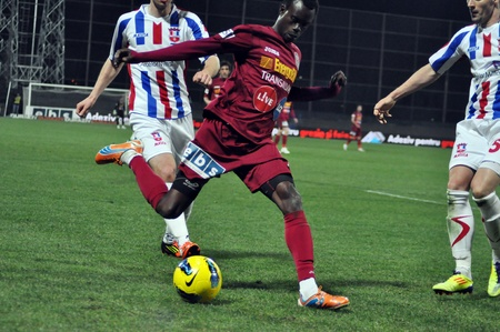 cfr cluj: CLUJ-NAPOCA, ROMANIA – MARCH 26: M. Sougou (in red) in action at a Romanian National Championship soccer game CFR Cluj vs. Otelul Galati, March 26, 2012 in Cluj-Napoca, Romania