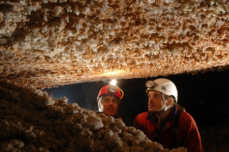 geologic: Beautiful stalactites in a cave with two speleologist explorers