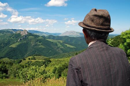 Viejo granjero en el prado en primavera