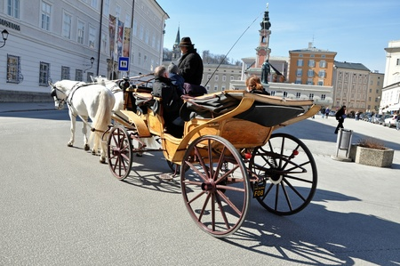 SALZBURG - MARCH 13: Horse driven carriage with tourists at Spring Days, visiting the famous city of Salzburg, part of Unesco heritage where the composer, W.A. Mozart was born. On March 13, 2012 in Salzburg, Austria Stock Photo - 12993552