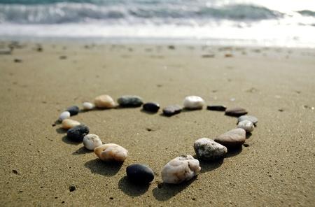 Hart gemaakt van kleine stenen op zand, op het strand