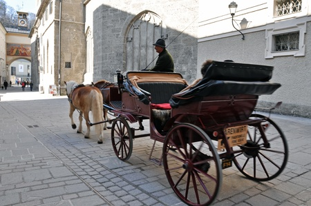 SALZBURG - MARCH 13: Horse driven carriage with tourists near the Franciscan church, visiting the famous city of Salzburg, part of Unesco heritage where composer W.A. Mozart was born. On March 13, 2012 in Salzburg, Austria