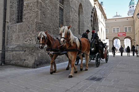 SALZBURG - MARCH 13: Horse driven carriage with tourists near the Franciscan church, visiting the famous city of Salzburg, part of Unesco heritage where composer W.A. Mozart was born. On March 13, 2012 in Salzburg, Austria Stock Photo - 13021750