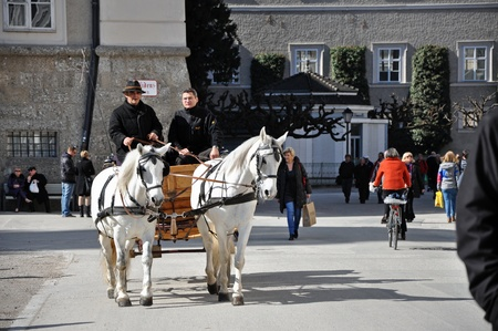 SALZBURG - MARCH 13: Horse driven carriage with tourists in Residenzplatz square, visiting the famous city of Salzburg, part of Unesco heritage where composer W.A. Mozart was born. On March 13, 2012 in Salzburg, Austria