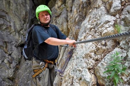 rockclimb: Young man climbing on via ferrata track