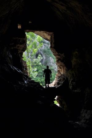 grotte: Silhouette d'un homme debout devant une entr�e de la grotte Banque d'images
