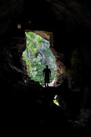 realm: Silhouette of a man standing in front of a cave entrance
