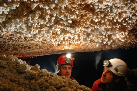 caving: Beautiful stalactites in a cave with two speleologist explorers